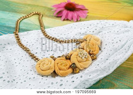 Handmade peach-colored necklace on a chain on the background of a lace dress