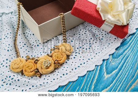 Handmade peach-colored necklace on a chain lies close to the gift box