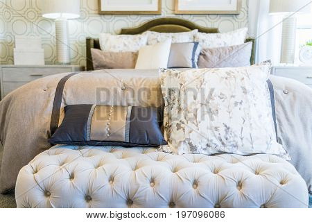 Modern Decorated Bed With Bench Rest And Many Pillows Closeup