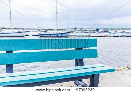 Empty Blue Bench Overlooking St Lawrence River In Quebec, Canada During Summer With Boats In Harbor