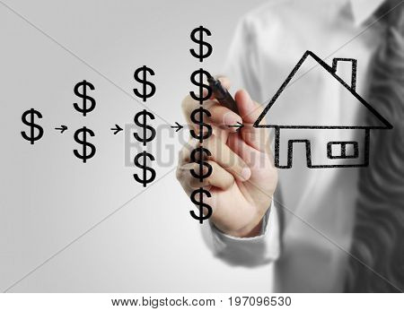 Businessman hand drawing a house