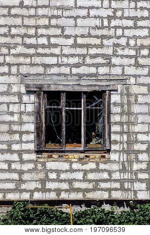 An old wooden window on the white brick wall of the house
