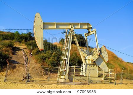 Pumpjack industrial mechanical equipment used to uplift oil from an Oil Well taken in a field