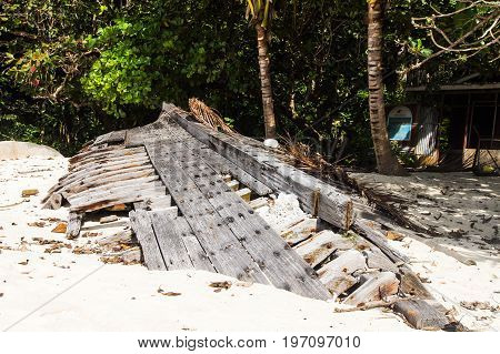 Ruined skeleton of an old boat on the shore of a tropical island. Pulau Perhentian Malaysia.