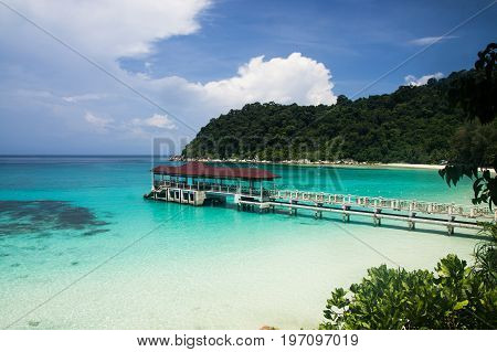 Relax on a deserted beach in an island of Tropical paradise. White sand Turtle beach with pier at Pulau Perhentian Malaysia.