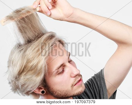 Man With Stylish Haircut Combing His Hair