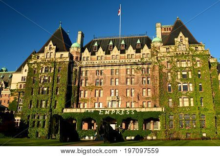 Victoria BC,Canada,May 23rd 2014.The iconic Empress hotel in Victoria BC is first class accommodations when staying in Victoria.The Empress facade with ivy climbing on the hotel and the proud Canadian flag on top.Come to Victoria and stay at the Empress.