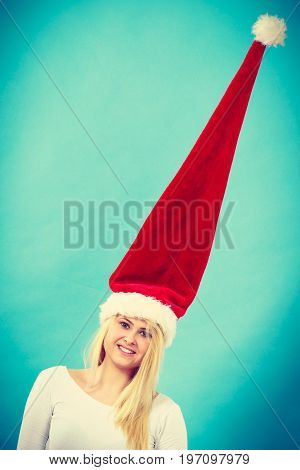 Young woman teen girl wearing blowing windblown santa claus hat. Crazy joyful girl having fun. Christmas time. Studio shot on blue