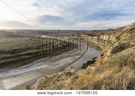 Bluffs reflect in the water and animal tracks follow the river as the Little Missouri River flows through Theodore Roosevelt National Park