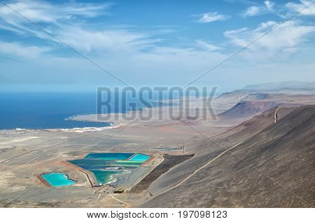 Aerial view to industrial colorful pools desert mountains and ocean