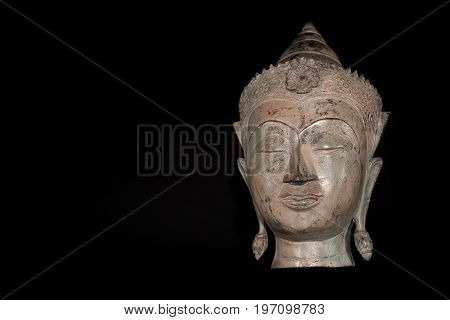 Buddha head. Classic traditional zen buddhism statue isolated against black background. Spiritual enlightenment expressed in a serene comtemplative expression.