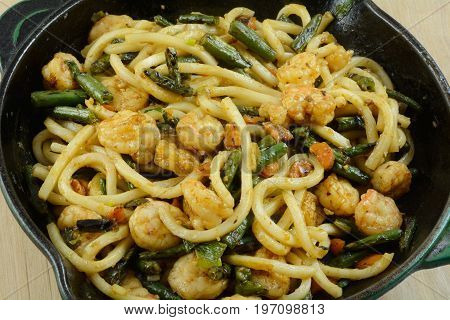 Shrimp lo mein with vegetables in cast iron frying pan skillet