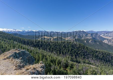 A clear blue sky above snow-capped peaks of the Rocky Mountains near Yellowstone