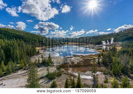 A pond in Yellowstone is heated by thermal features under a blue sky with white clouds.