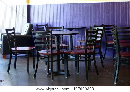 chairs and tables next to sunny window at cafe