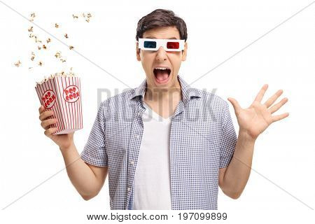 Terrified guy with a pair of 3D glasses and popcorn isolated on white background