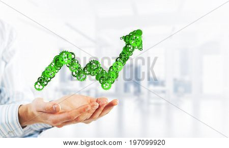 Close of hands holding in palms growing graph made of gears