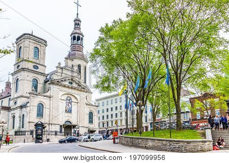 Quebec City Canada - May 29 2017: Old town street with flags and garden park called Place de l'Hotel-de-Ville and Notre Dame Cathedral