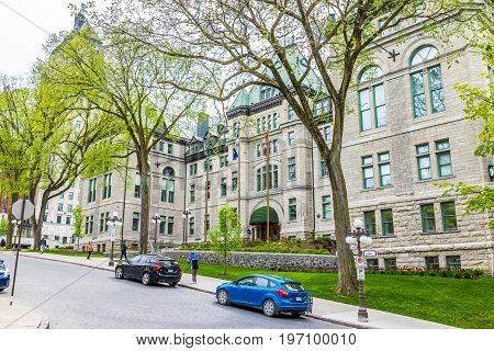 Quebec City Canada - May 29 2017: Old town street with Hotel de Ville City Hall cobblestone road with flags