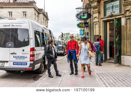 Quebec City, Canada - May 29, 2017: Old Town Street With Shops And Stores With People Walking By Bus