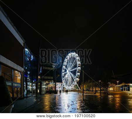 BRISTOL, UNITED KINGDOM - 5 MAR 2017: Sky View Observation Wheel in Anchor Square in central Bristol at night with people silhouette walking nearby on a rainy day