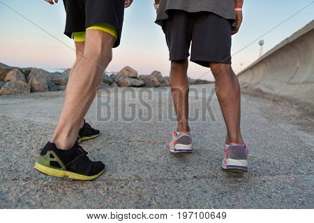 Back view of two male runners in sneakers outdoors
