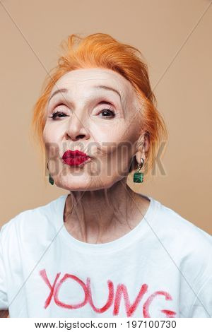 Photo of mature redhead fashion woman sitting isolated at studio posing. Looking camera blowing kisses.
