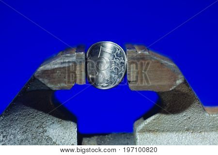 The coin in vise on the blue background as a symbol of economic sanction against of Russia
