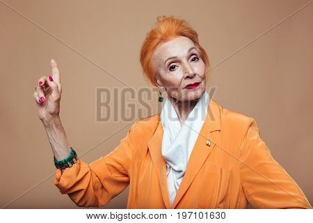 Photo of attractive mature redhead fashion woman standing isolated at studio and pointing. Looking at camera.