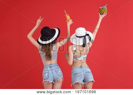 Back view picture of young two women standing isolated over red background drinking cocktails.