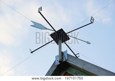 Weathervane Against A Radiant Blue Sky. The Sides Of The World Are Marked With Cyrillic Letters. Wea