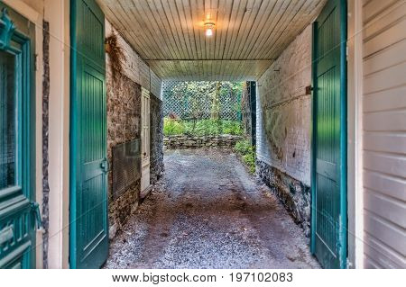 Old Narrow Dark Brick White And Green Alleyway With Path To Garden