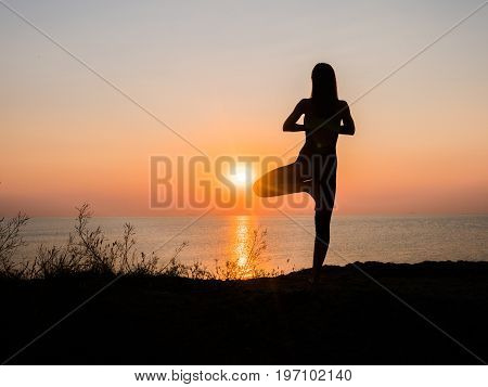 Morning exercise. Twine. Yoga mat woman stretching hip, hamstring muscles and groin area. Fit fitness athlete girl exercising sports stretches in active wear on beach at sunset.