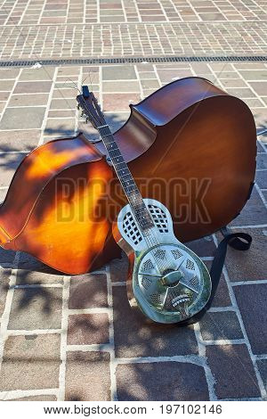 Metallic resonator acoustic guitar leaning on a cello. Also known as National.