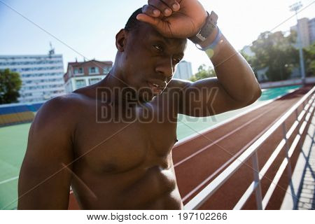 Close up of a young exhausted african athlete man resting while leaning on a railing at the stadium