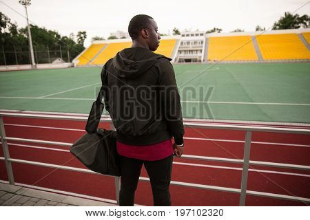 Back view of a young african sportsman with bag standing at the open stadium