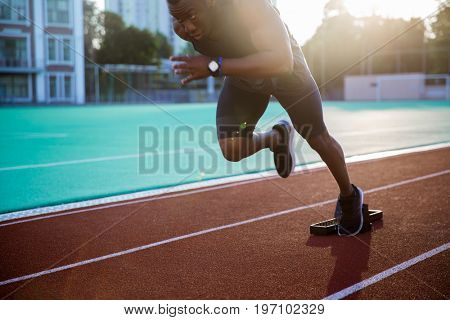 Cropped image of a young african male athlete launching off the start line in a race