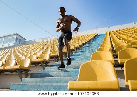 Sporty young african man runner running downstairs at the stadium