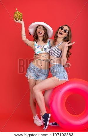 Photo of happy young ladies with rubber ring and cocktail posing isolated over red background. Looking camera.