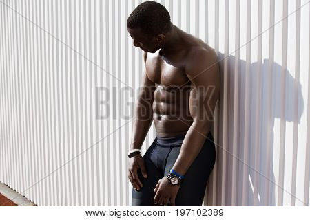 Young tired afro american sportsman resting against white wall