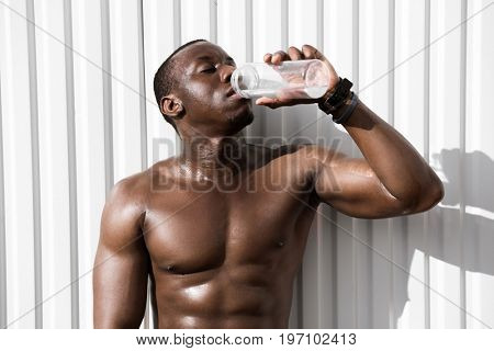 Portrait of a young thirsty african sportsman drinking water against white wall