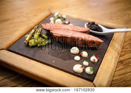 Grilled duck breast with asparagus served on a stone board