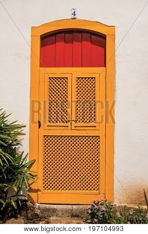 Paraty, Brazil - January 26, 2015. Close-up of colorful door in a cobblestone alley and vegetation in Paraty, an amazing and historic town totally preserved in the coast of the Rio de Janeiro State, southwestern Brazil