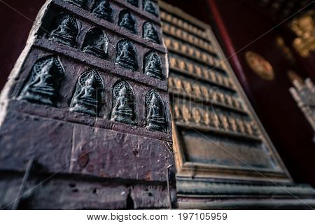 Wooden carving buddha images inside of Wat Xieng Thong Buddhist temple in Luang Prabang Laos.
