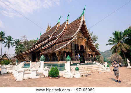 LUANG PRABANG LAOS - MARCH 11 2017: Tourists visiting the Wat Xieng Thong Buddhist temple located in the city Luang Prabang capital of Laos.