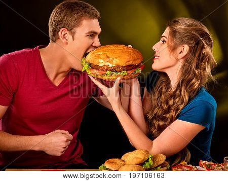 Couple eating fast food. Man and woman treat big hamburger with ham. Friends give burder junk on dark background . Enamored people eat huge sandwich. How to feed the husband.