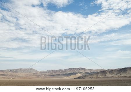 Arid lands of the desert under blue cloudy sky