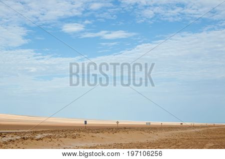 Road in desert with numerous road signs under blue sky