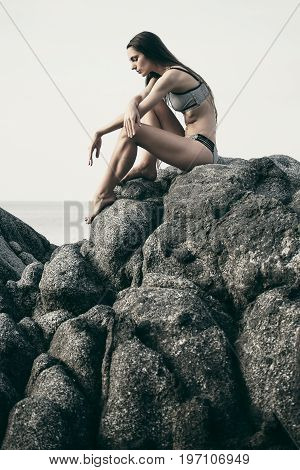 Beautiful woman sitting at the rock by seaside