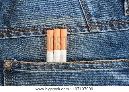 Three Cigarettes So Close Are In The Back Pocket Of Blue Jeans